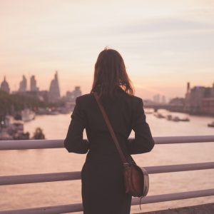 A young woman with a shoulderbag is standing on a bridge and is admiring the sunrise over the London skyline