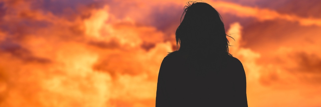 silhouette of woman looking at sunset sky