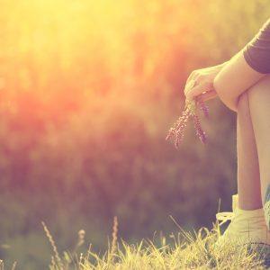 girl sitting in grass with sun shining