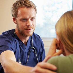 male doctor talking to female patient