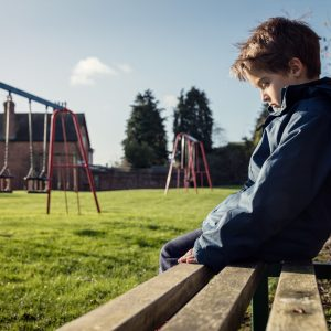 Lonely child sitting on playground bench.