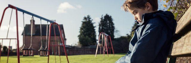 Lonely child sitting on playground bench.
