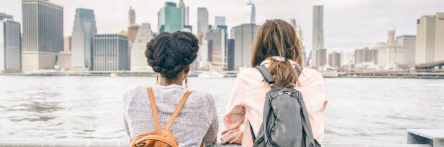 Two women leaning on railing, looking at city skyline and water
