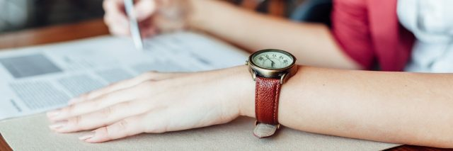woman signing contract wearing leather wristwatch