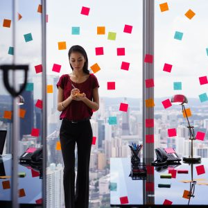 Woman writing post it notes and sticking them on large window.