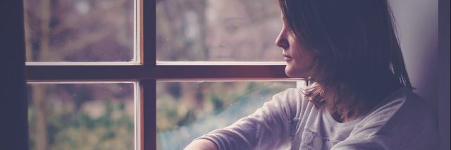 young woman looking out window lonely sad