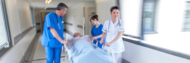 emergency room staff wheeling a patient down a hallway on a gurney