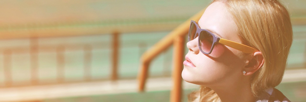 Woman outside wearing sunglasses, wit a thoughtful expression.