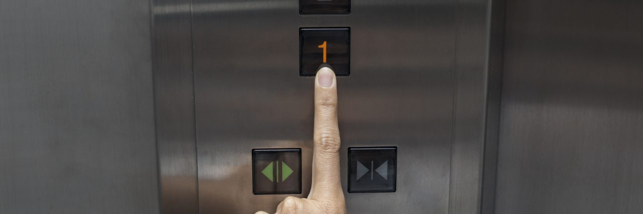 "Woman's hand pressing number ""one"" on an elevator."