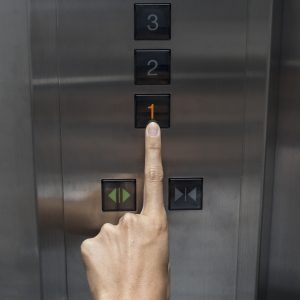 """Woman's hand pressing number """"one"""" on an elevator."""