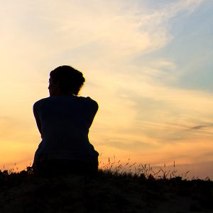 Silhouette of woman sitting on grass in front of sunset sky