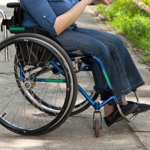 Girl in wheelchair sitting outside.