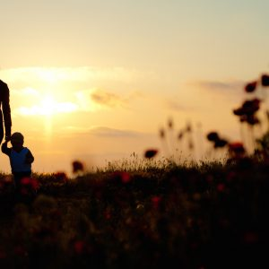 Mom holding hands with two children near a grassy area at sunset