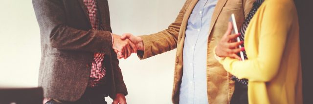 man shaking hands with another man, woman next to them