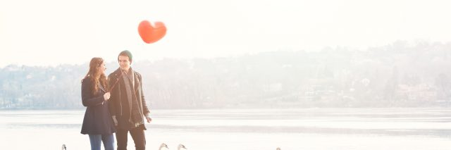 Cute young couple in love, walking at the riverside, with a red balloon and swans