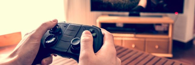 Hands holding game pad and playing shooter game on tv screen.