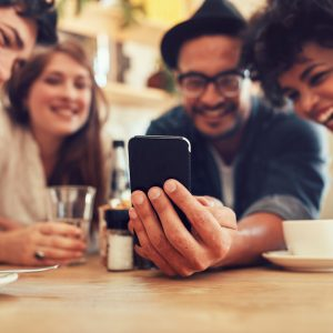Group of friends at table, looking at smart phone