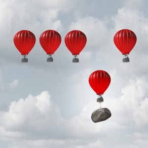 Hot air balloons floating in sky, one being held back due to rock weighing it down.