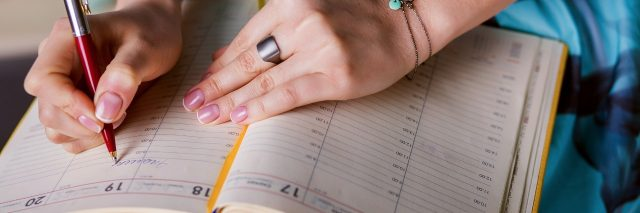 woman in blue dress writing her schedule in a day planner