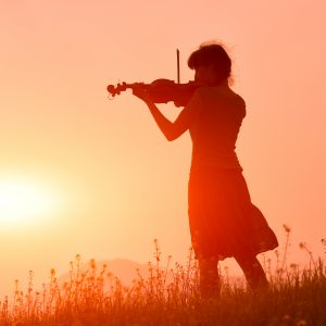woman playing a violin in a field in front of a sunset