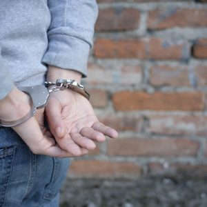 Photo of a man arrested with hands cuffed behind his back