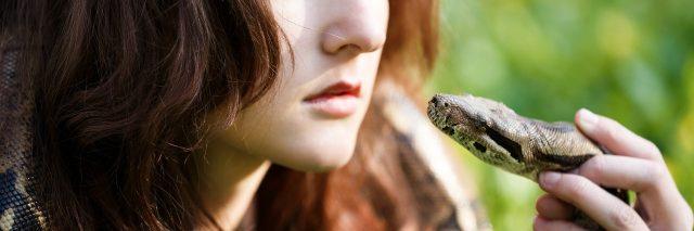 Teenage girl holding snake near face