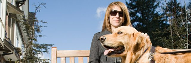Blind woman sitting on a bench on a sunny day with her golden retriever guide dog.