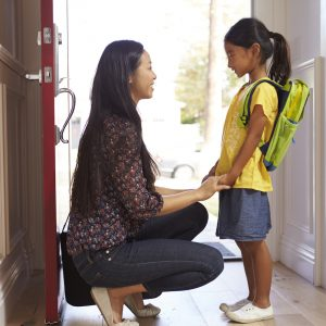 Mother and daughter in front of open door at home, with daughter wearing backpack, and mom holding daughter's hands