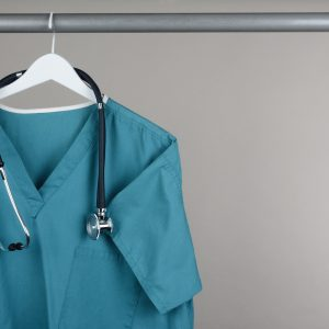 A nurse's scrub shirt hanging up in a closet