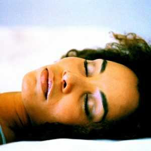 Close-up shot of the face of a young woman sleeping on a bed