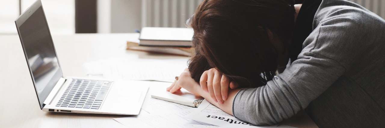 woman with her head down asleep at her desk