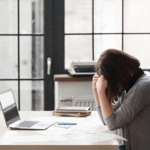 stressed business woman at office with head in hands