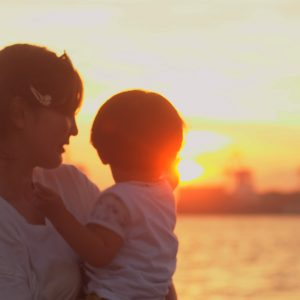 Mother holding child, with water and sunset landscape in the background