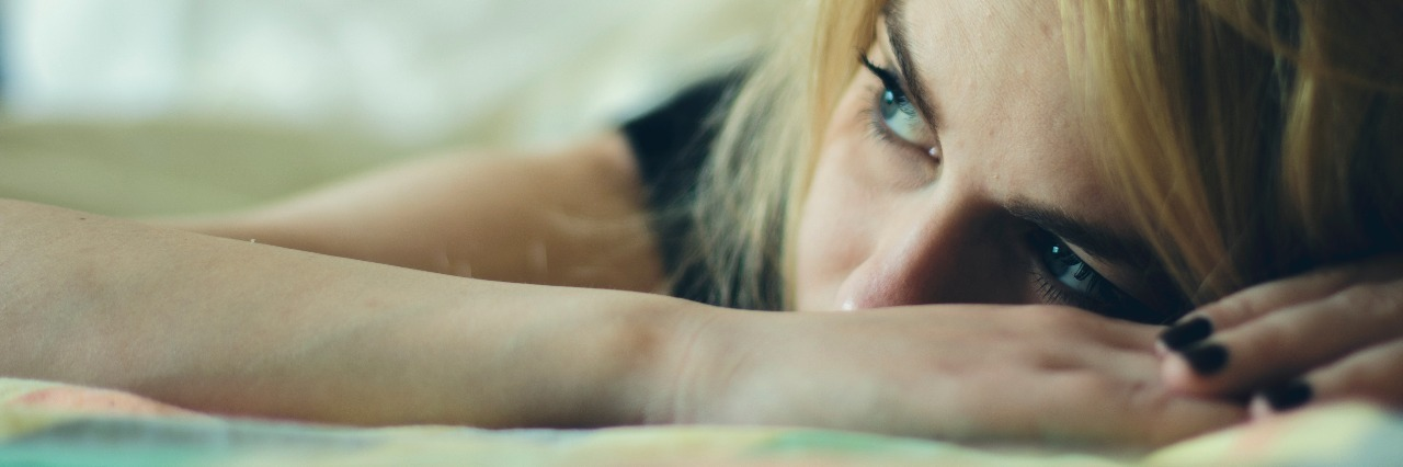 woman with blonde hair lying in bed looking upset
