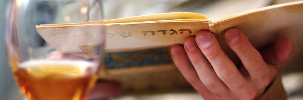 man reading haggadah book during passover seder dinner