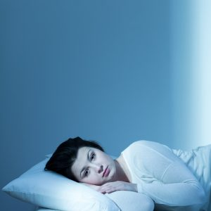 tired young woman lying in bed with eyes open