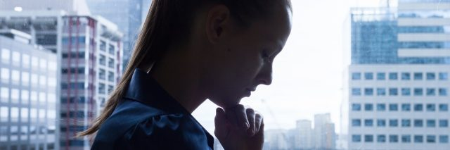 silhouette of upset woman standing next to a window overlooking the city