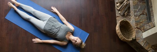 young woman performing yoga savasana pose relaxation on wooden floor near window
