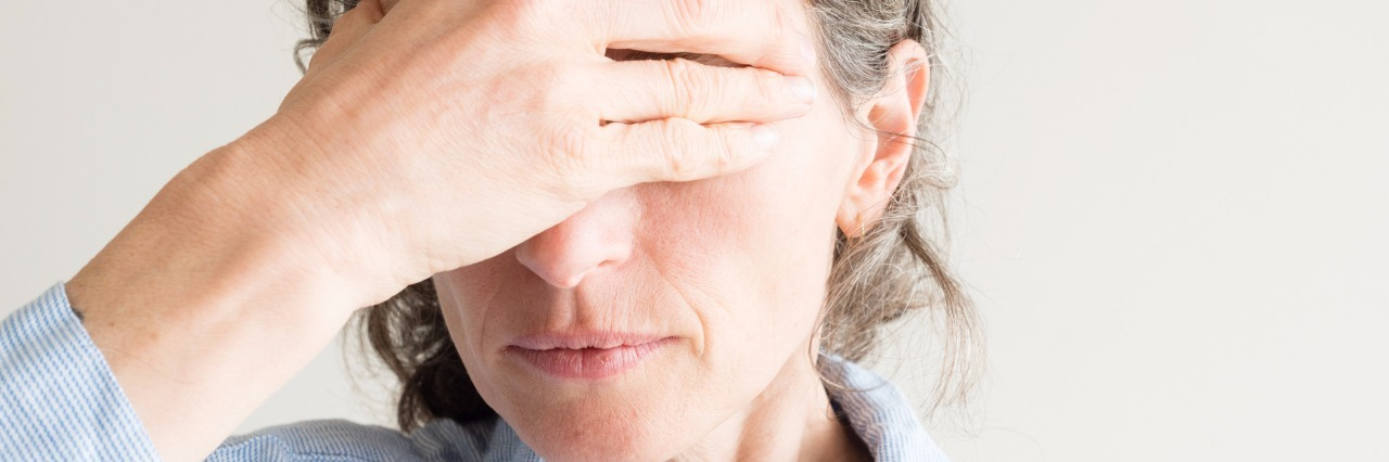 woman covering her eyes with her hand in grief
