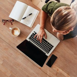 bird's eye view of a woman sitting at a table and typing on her laptop