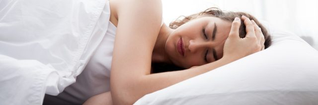 woman lying in bed holding her head in pain