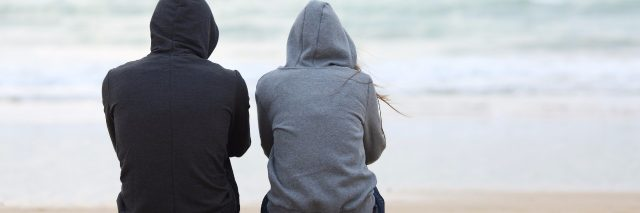 two teenagers on beach sitting back to back staring at ocean bad weather