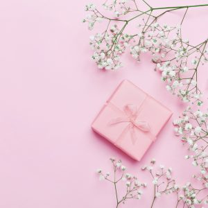 Gift or present box and flower on pink table from above. Pastel color.
