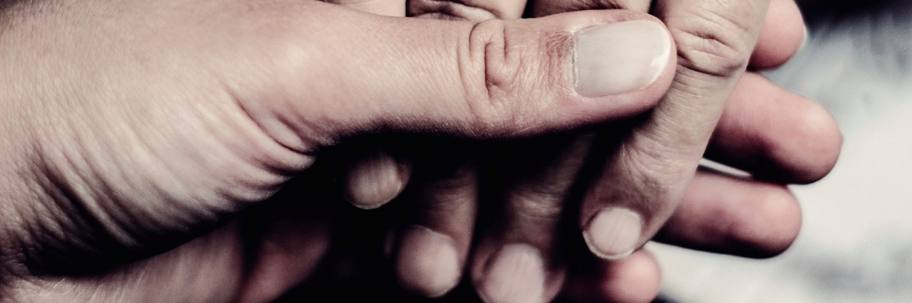 Close-up of two people holding each other's hands
