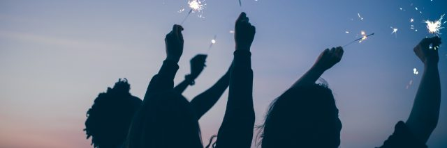 Friends celebrate new year's eve party with sparklers and firework at sunset