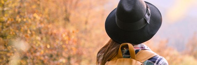 Woman wearing hat and backpack, walking near autumn trees in park