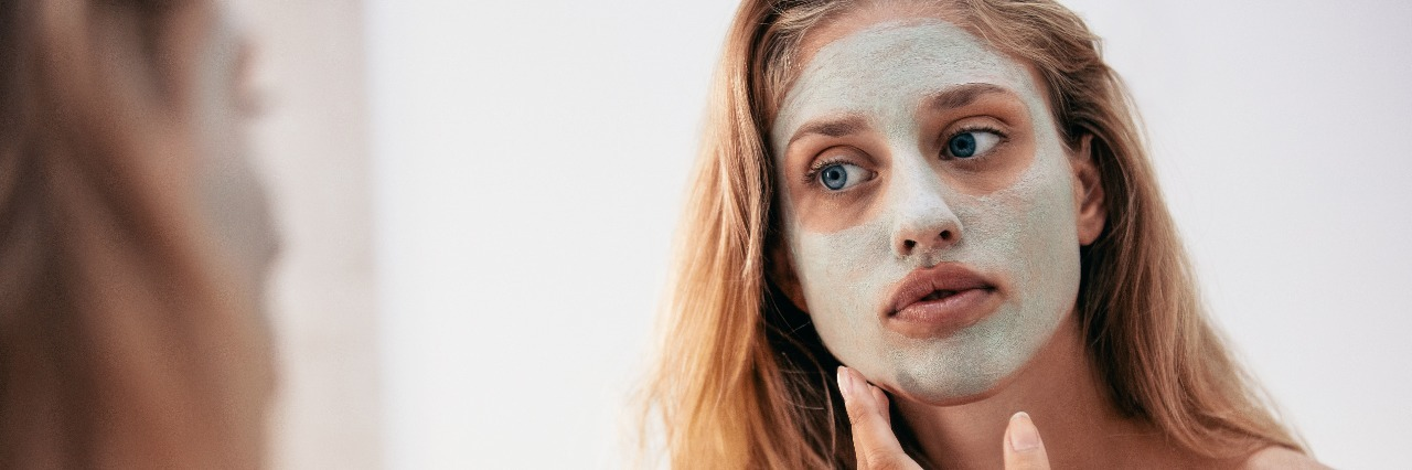 blonde woman looking into mirror applying face mask