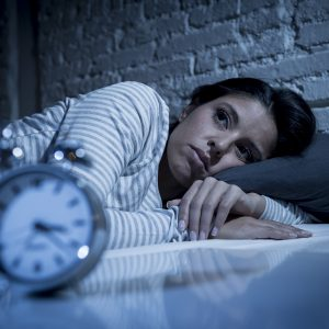 woman lying in bed with eyes open next to a clock