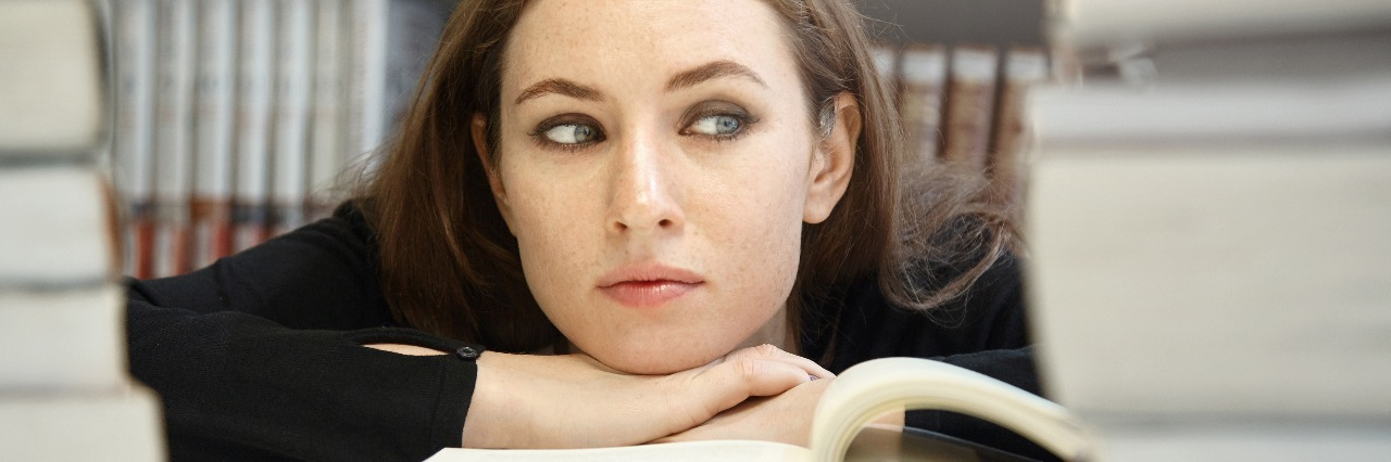 female college student surrounded by books looking tired