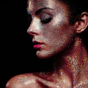 Portrait of beautiful woman with sparkles on her face.